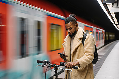 Stylish man with a bicycle and smartphone in a metro station - p300m2180023 by Hernandez and Sorokina