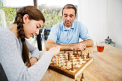 Father and daughter playing chess at home - p300m977873f by Gabi Dilly