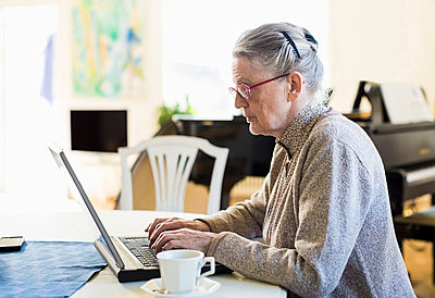 Side view of senior woman using laptop at table - p426m844614f by Maskot