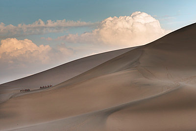 Tourists and camels climbing the slopes of Singing Sand mountain; Jiuquan, Gansu, China - p442m824153 by Keith Levit