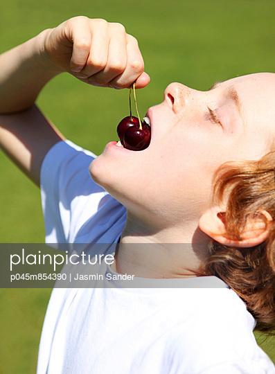 Boy eating cherries - p045m854390 by Jasmin Sander