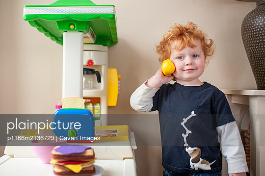 Toddler boy looking while answering phone in play kitchen at home - p1166m2136729 by Cavan Images