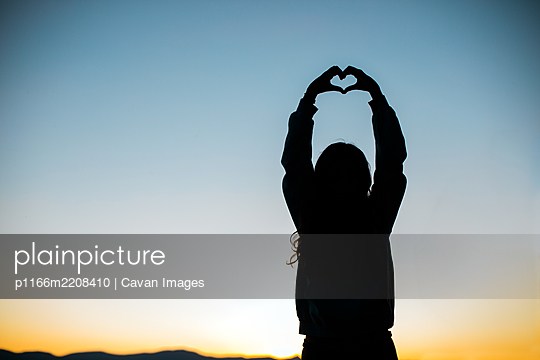 Hands form a Heart for Love Silhouette with Sunset or Sunrise - p1166m2208410 by Cavan Images