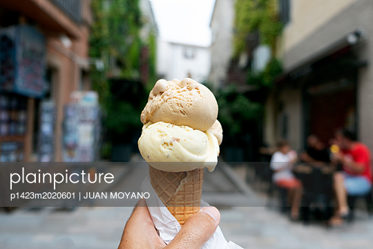 Man with an ice cream in the street - p1423m2020601 by JUAN MOYANO