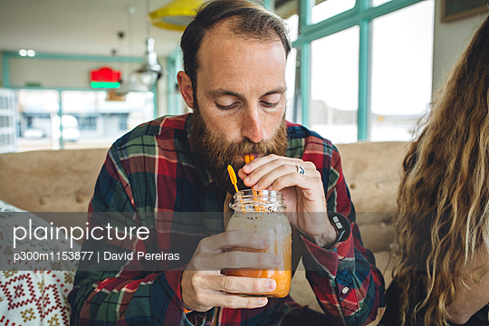 Bearded man drinking organic juice in cafe - p300m1153877 by David Pereiras
