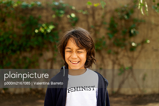 Laughing boy standing in the street with print on t-shirt, saying Feminist - p300m2167085 by Valentina Barreto