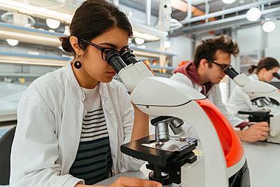 Laboratory technicians using microscopes in lab - p300m1416485 by Zeljko Dangubic
