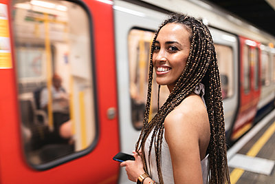 Portrait of happy young woman waiting at subway station platform, London, UK - p300m2132656 by William Perugini