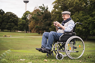 Happy senior man sitting in wheelchair on a meadow using smartphone - p300m2144894 von Uwe Umstätter