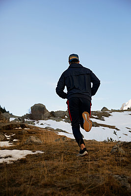 Young male athlete jogging on mountain in winter - p300m2250034 by Aitor Carrera Porté