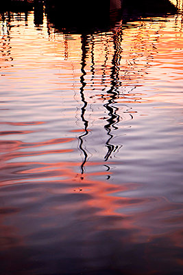 Reflections of sailing boat masts in harbour water - p597m2142977 by Tim Robinson