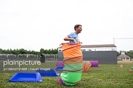 Smiling Tween Boy Plays Lawn Games During Field Day at School - p1166m2191888 by Cavan Images