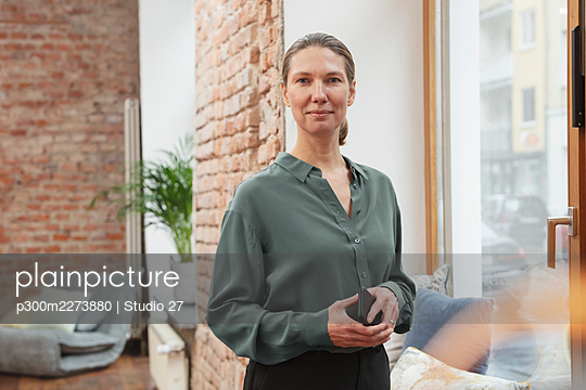 Contented businesswoman holding smart phone while standing by window in office - p300m2273880 by Studio 27