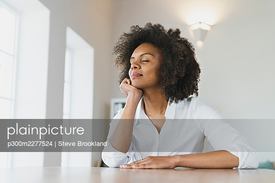 Young woman with hand on chin day dreaming at home - p300m2277524 by Steve Brookland