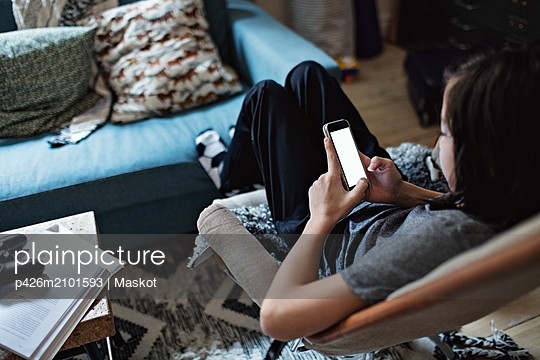 High angle view of boy using mobile phone while sitting in living room - p426m2101593 by Maskot