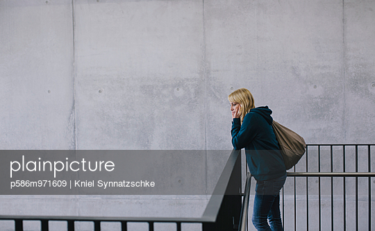 Blonde Studentin lehnt an einem Geländer - p586m971609 von Kniel Synnatzschke
