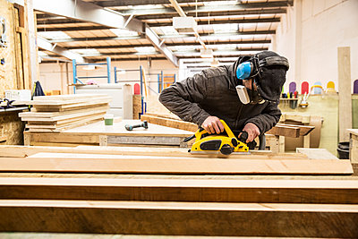 Man wearing ear protectors, protective goggles and dust mask standing in a warehouse, sanding planks of recycled wood. - p1100m1575740 by Mint Images