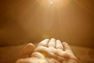 Sunbeams falling on cropped hand of woman - p1166m1546841 by Cavan Images