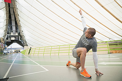 Runner stretching on indoor track - p1192m1129676f by Hero Images