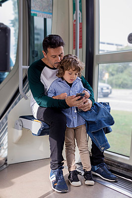 Father and son using cell phone in a tram - p300m2070407 von Mauro Grigollo