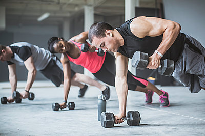 Athletes doing push-ups with dumbbells on floor - p555m1411967 by John Fedele