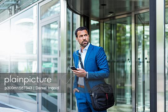 Businessman with smartphone, earphones and laptop bag - p300m1587343 von Daniel Ingold