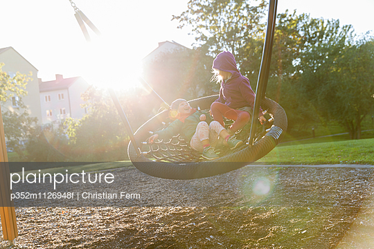 Sweden, Sodermanland, Arsta, Little boy (4-5) and girl (2-3) in round swing at sunlight