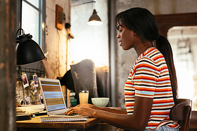 Young woman sitting at desk in a loft working on laptop - p300m1580949 by Bonninstudio
