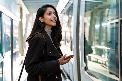 Smiling young woman with smartphone at the tram stop - p300m2166181 by VITTA GALLERY