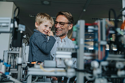Smiling male scientist showing machinery to son in laboratory at factory - p300m2206956 by Mareen Fischinger
