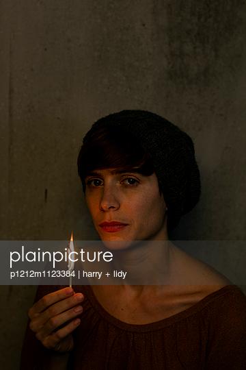 Frau mit brennendem Streichholz - p1212m1123384 von harry + lidy