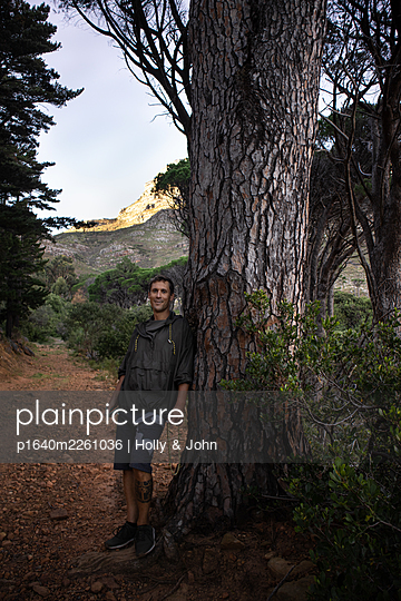 Hiker leaning against pine - p1640m2261036 by Holly & John