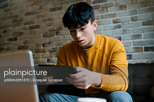 Young man with laptop using digital tablet while sitting at cafe - p300m2251370 by Ezequiel Giménez