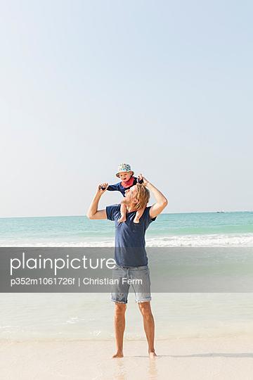 United Arab Emirates, Dubai, Man carrying son (12-17 months) on beach