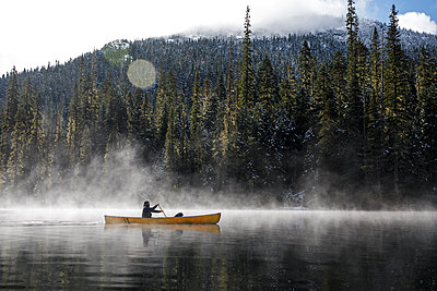 Man paddles canoe on lake with mist and fog on sunny day by forest - p1166m2235119 by Cavan Images