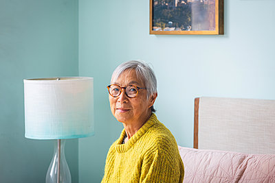 Smiling senior woman wearing yellow sweater sitting in bedroom at home - p1166m2285608 by Cavan Images