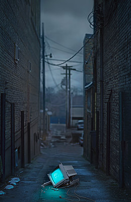 Glowing television in abandoned urban alleyway - p555m1454185 by Chris Clor