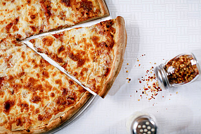 Pizza slice with spilled chili flakes - p924m807340f by Chad Springer