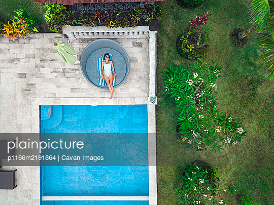 Aerial view of attractive woman near the pool at resort - p1166m2191864 by Cavan Images