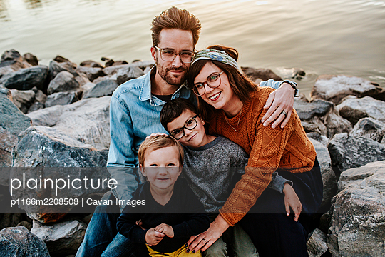 Center portrait of a young family sitting on rocks near a lake - p1166m2208508 by Cavan Images