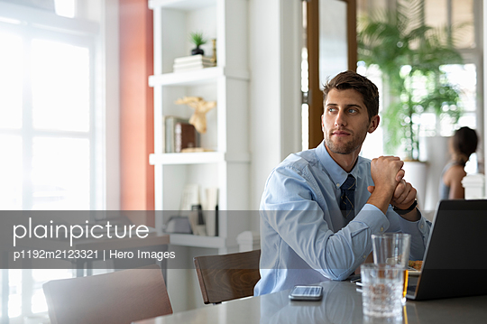 Businessman on working lunch with laptop looking away - p1192m2123321 by Hero Images