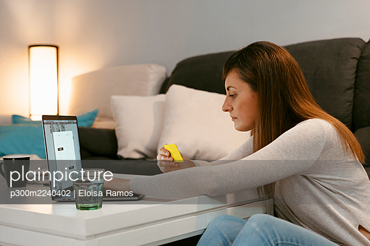 Mid adult woman with credit card shopping online on laptop while sitting at home - p300m2240402 by Eloisa Ramos