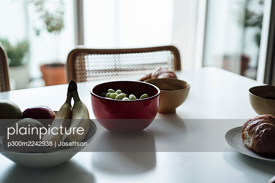 Fruits and croissant in bowl on dining table at apartment - p300m2242938 by Joseffson