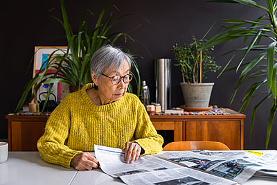Senior woman wearing yellow sweater reading newspaper at home - p1166m2285614 by Cavan Images