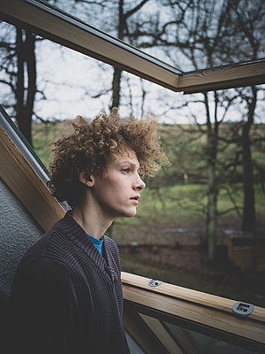 Junger Mann schaut aus dem Fenster - p1267m2090144 von Wolf Meier