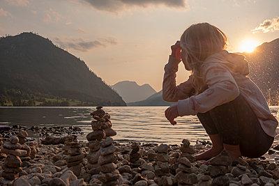 Austria, Ausseer Land, Girl building cairns at lakeshore - p300m2060037 by Hans Mitterer