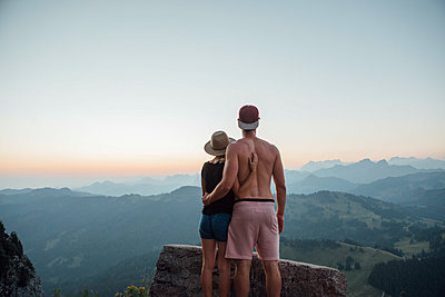 Switzerland, Grosser Mythen, young couple on a hiking trip at sunrise looking at view - p300m2062056 by letizia haessig photography