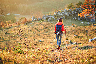 Rear view of woman walking on trail on a hiking trip in the mountains - p300m2083242 by Bartek Szewczyk