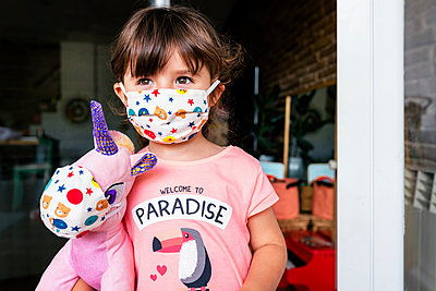 Portrait of girl with a colorful mask and a unicorn soft toy - p300m2188654 by Gemma Ferrando