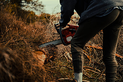 Teenage boy cutting wood with chainsaw in forest - p300m2264456 by Aitor Carrera Porté